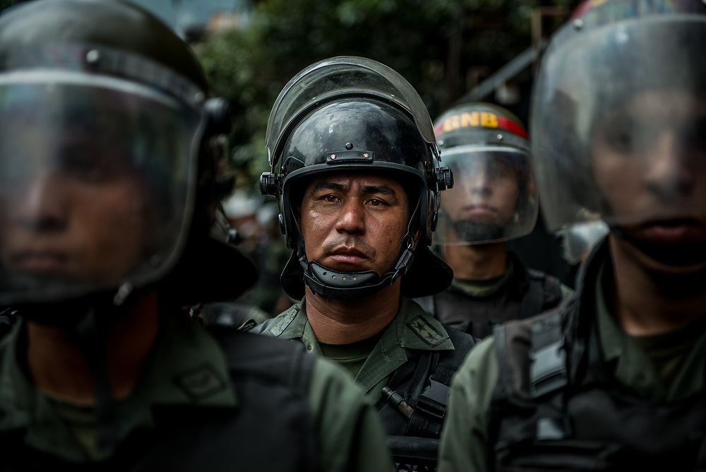 CARACAS, VENEZUELA - JUNE 2, 2017: Soldiers man a barricade and prohibit anti-government protesters from passing. The streets of Caracas and other cities across Venezuela have been filled with tens of thousands of demonstrators for nearly 100 days of massive protests, held since April 1st. Protesters are enraged at the government for becoming an increasingly repressive, authoritarian regime that has delayed elections, used armed government loyalist to threaten dissidents, called for the Constitution to be re-written to favor them, jailed and tortured protesters and members of the political opposition, and whose corruption and failed economic policy has caused the current economic crisis that has led to widespread food and medicine shortages across the country.  Independent local media report nearly 100 people have been killed during protests and protest-related riots and looting.  The government currently only officially reports 75 deaths.  Over 2,000 people have been injured, and over 3,000 protesters have been detained by authorities.  PHOTO: Meridith Kohut