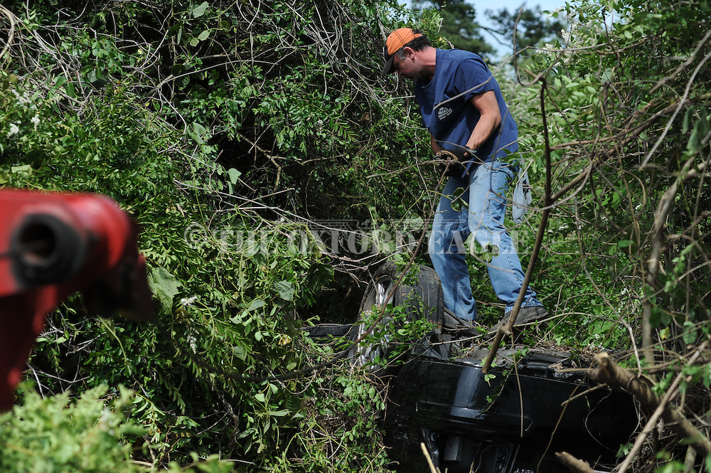 A Volvo car is removed from the trees along the east side of Highway 7 near the Highway 30 interchange in Oxford, Miss. on Wednesday, April 25, 2012.