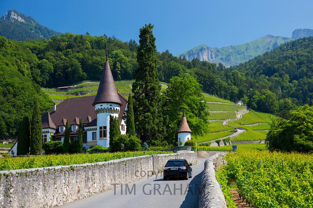 Suburu hatchback car passes wine estate, Chateau Maison Blanche, at Yvorne in the Chablais region of Switzerland