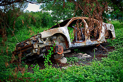 27 August 2014. Lower 9th Ward, New Orleans, Louisiana.<br /> Hurricane Katrina 9 years later. A burned out wreck of a car languishes on a vacant lot as the area continues to struggle with recovery from Hurricane Katrina.<br /> Photo; Charlie Varley/varleypix.com
