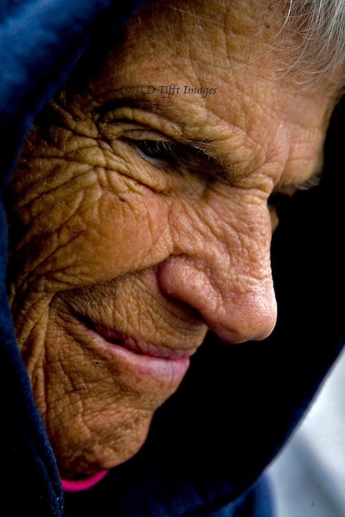 Tight head shot of a smiling elderly woman in a dark hood.  Only her profile is visible.