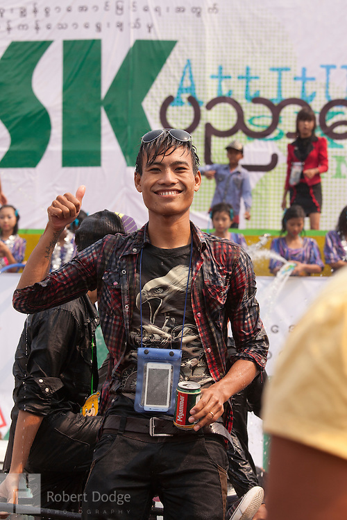 Mandalay, Myanmar- April 14, 2013: A young man smiles as he celebrates during Myanmar's Thingyan Water Festival. Thingyan is held in April, one of the hottest months of the year in Myanmar. The water festival marks the country's New Year celebration and the festival includes lots of drinking, singing, dancing and theater. Wherever you are you are likely to get doused with water as the Burmese see this as a cleansing of the previous year's sins and bad luck and a blessing for good luck and prosperity in the year ahead. In the major cities of Mandalay and Yangon, large platforms are erected along major roadways and are equipped with high powered water hoses. The platforms, sponsored by large corporate donors, also have dance stages and play the latest pop and hip hop music. Thousands of residents pour into the streets by foot, motorbike and flatbed truck to get hosed under the platforms while they drink and dance. Many of the young celebrants wear their best clubbing clothes. And many of the party goers are men, having left their wives and girlfriends at home.