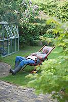 Gardener sleeps on deckchair in back garden