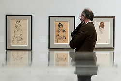 """© Licensed to London News Pictures. 31/10/2018. LONDON, UK. A visitor views (L to R) """"Maria Steiner"""", 1918, """"Marie Schiele"""", 1918, and """"Edith Schiele"""", 1917, all by Egon Schiele. Preview of """"Klimt / Schiele:  Drawings from the Albertina Museum,Vienna"""" exhibition at the Royal Academy.  Over 100 works on paper are on display in an exhibition which marks the centenary of the deaths of the two most celebrated and pioneering figures of early twentieth-century art.  The show runs 4 November to 3 February 2019.  Photo credit: Stephen Chung/LNP"""