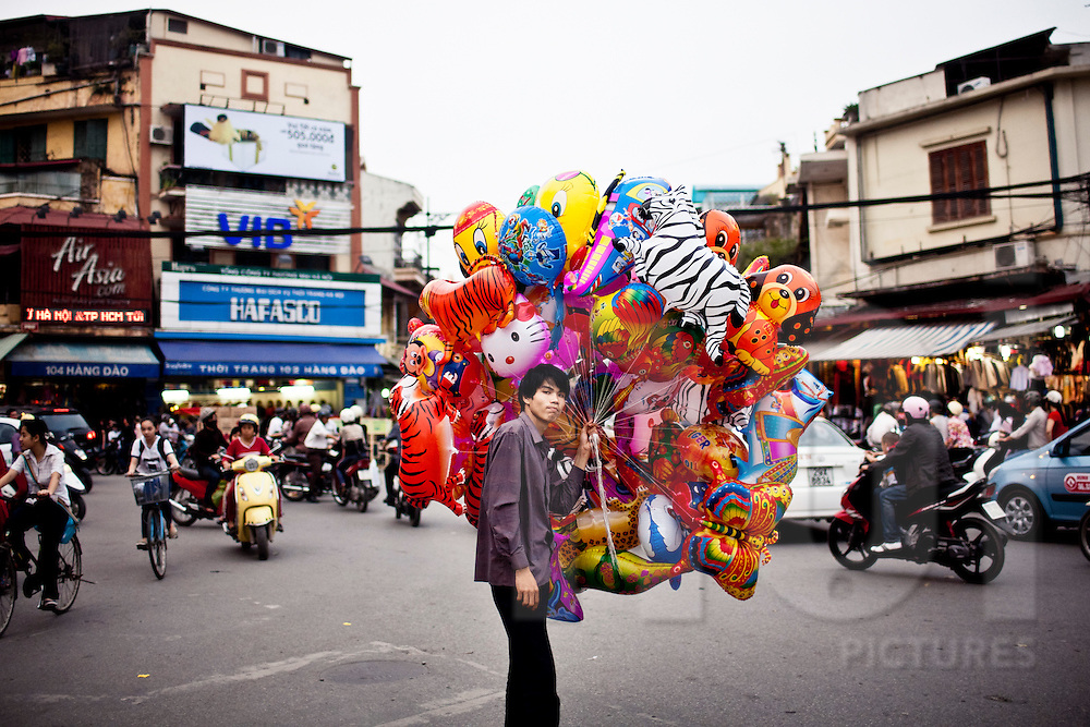 A young Vietnamese street vendor sells multicolored balloons at a busy crossroad of Hanoi, Vietnam, Southeast Asia