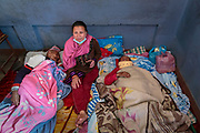 Inside a school, set up as a temporary refugee camp for internally displaced people, 72 year old Ram Shilpakar recovers from a broken ribs and head trauma sustained during the 2015 Nepal earthquake.