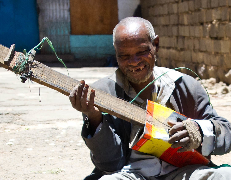 Beggar playing home made tin-can guitar