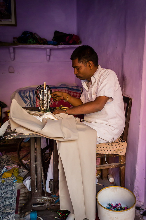 A tailor sews a piece of fabric in his purple workshop.