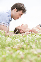 Side view of young man looking at woman sleeping on grass