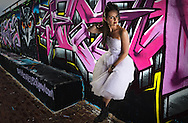 A bride poses in her wedding dress against a wall covered with graffiti.   Images by Paul Gregg a Durban portrait and fashion / lifestyle photographer.