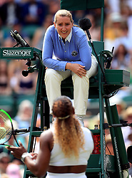 Chair umpire Aurelie Tourte speaks to Serena Williams after she penalises her for playing a shot on the wrong side of the net on day seven of the Wimbledon Championships at the All England Lawn Tennis and Croquet Club, Wimbledon.