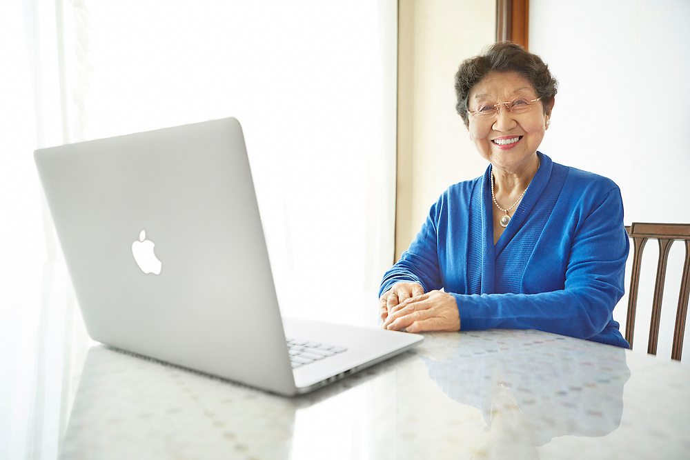 Lifestyle image of smiling Asian senior woman sitting inside hour with Apple Macbook Pro Mac Laptop