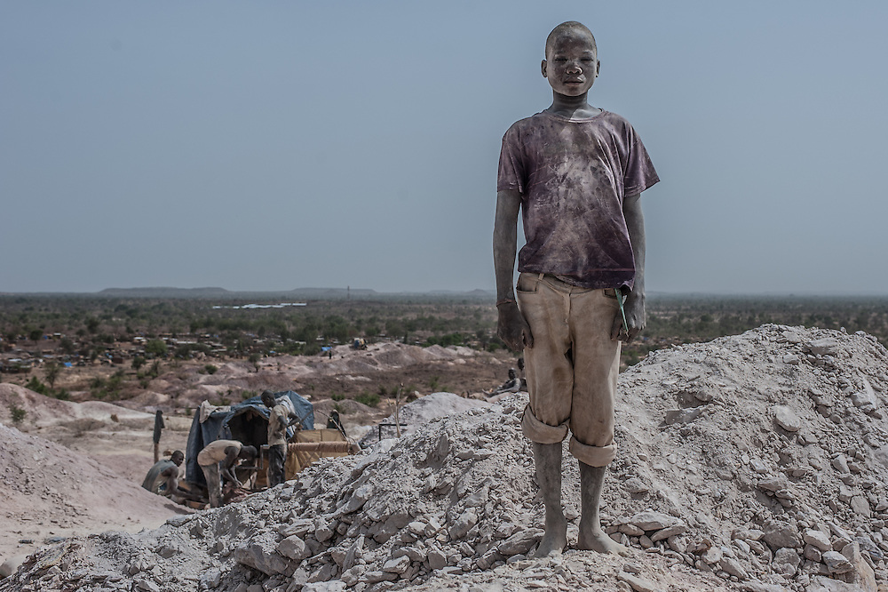 Nobsin, Burkina Faso - 13 May 2014: Abdou, 15, poses for a portrait at the gold extraction site. The youngest ones, small enough to reach the bottom of the mine shafts, are most often the victims of the recurrent accidents. Facing repeated physical and ver- bal violence, drinking alcohol and taking heavy drugs, without any aspiration to get an education, these small boys trying their luck with gold, are the most worri- some aspect of the Burkinabè artisanal gold rush.