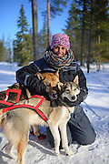 Young woman receives love from friendly dogs. Wilderness husky sledding taiga tour with Bearhillhusky in Rovaniemi, Lapland, Finland