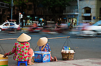 Two street vendors sitting on the side of the road in Saigon.