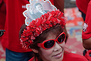 """Mar. 26, 2009 -- BANGKOK, THAILAND: A woman wore a hat with a picture of ousted Thai Prime Minister  Thaksin Shinawatra at a rally of his supports in Bangkok Thursday. More than 30,000 members of the United Front of Democracy Against Dictatorship (UDD), also known as the """"Red Shirts""""  and their supporters descended on central Bangkok Thursday to protest against and demand the resignation of current Thai Prime Minister Abhisit Vejjajiva and his government. Abhisit was not at Government House Thursday. The protest is a continuation of protests the Red Shirts have been holding across Thailand in March.  Photo by Jack Kurtz"""