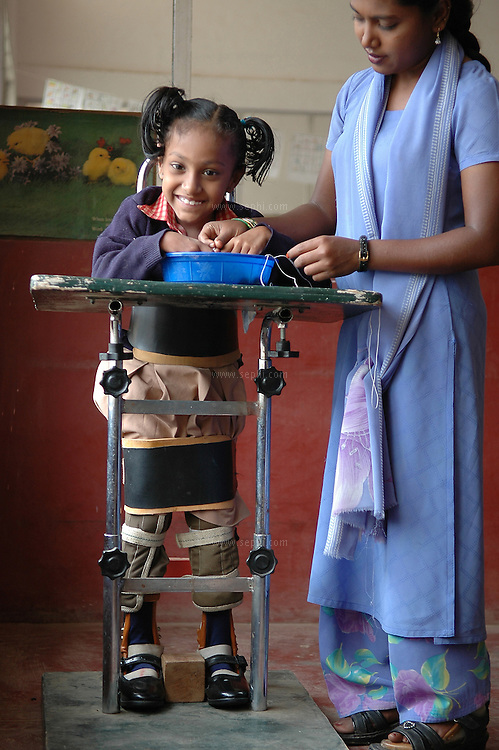 Rachel (6) suffers from Cerebral palsy in four limbs and cannot stand without help. Here with her physiotherapist Shaheena, strapped in the standing harness as a part of the physiotherapy plan at APD School in Bangalore.