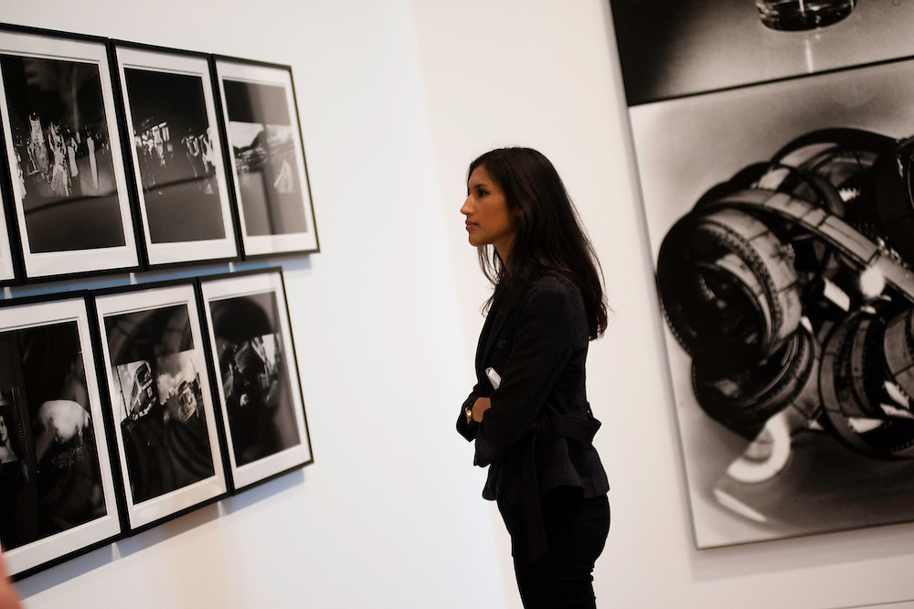 London, UK - 8 October 2012: a woman looks up at pictures by Daido Moriyama. The exhibition examine the relationship between the work of William Klein (b.1928) and that of Daido Moriyama (b.1938). Taking as its central theme the cities of New York and Tokyo, the show explores both artists' celebrated depictions of modern urban life.