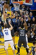 Golden State Warriors center Zaza Pachulia (27) takes the ball to the basket against Dallas Mavericks forward Dirk Nowitzki (41) at Oracle Arena in Oakland, California, on February 8, 2018. (Stan Olszewski/Special to S.F. Examiner)
