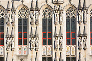 Traditional architecture statues, carved stonework, crests and windows in Bruges - Brugge - Belgium