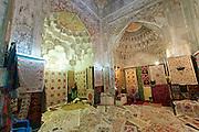 Uzbekistan, Bukhara. Abdul Aziz Khan Medressa. Souvenir shops in students' cells. Rugs.