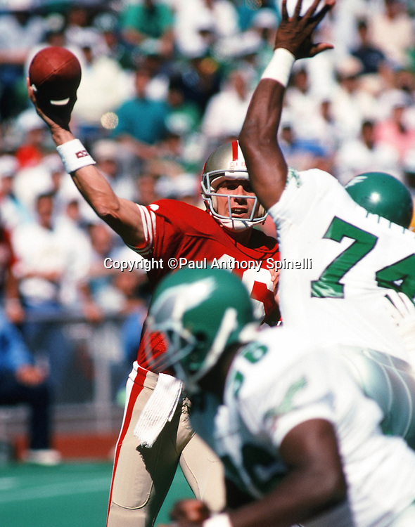 San Francisco 49ers quarterback Joe Montana (16) throws a pass despite the outstretched arm of a defender during the NFL football game against the Philadelphia Eagles on Sept. 24, 1989 in Philadelphia. The 49ers won the game 38-28. (©Paul Anthony Spinelli)