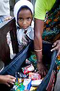 As her daughter Mahfuza Akhter (5) looks on, Shahida Begum, 35, looks into her product bag in her hut's compound in Palashbari Villlage, Taragonj, Rangpur, Bangladesh on 18th September 2011, after a regular day of work as a saleswoman earning 3500 - 5000 Bangladeshi Taka per month. She is one of many rural Bangladeshi women trained by NGO CARE Bangladesh as part of their project on empowering women in this traditionally patriarchal society. Named 'Aparajitas', which means 'women who never accept defeat', these women are trained to sell products in their villages and others around them from door-to-door, bringing global products from brands such as BATA, Unilever and GDFL to the most remote of villages, and bringing social and financial empowerment to themselves.  Photo by Suzanne Lee for The Guardian