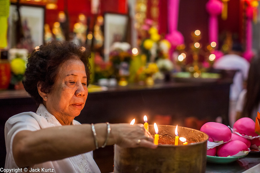 22 OCTOBER 2012 - HAT YAI, THAILAND:      A woman lights candles for prayer at a Chinese temple in Hat Yai. Hat Yai is the largest city in southern Thailand. It is an important commercial center and tourist destination. It is especially popular with Malaysian, Singaporean and Chinese tourists.     PHOTO BY JACK KURTZ