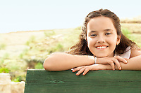 Girl (10-12) leaning on railing portrait.