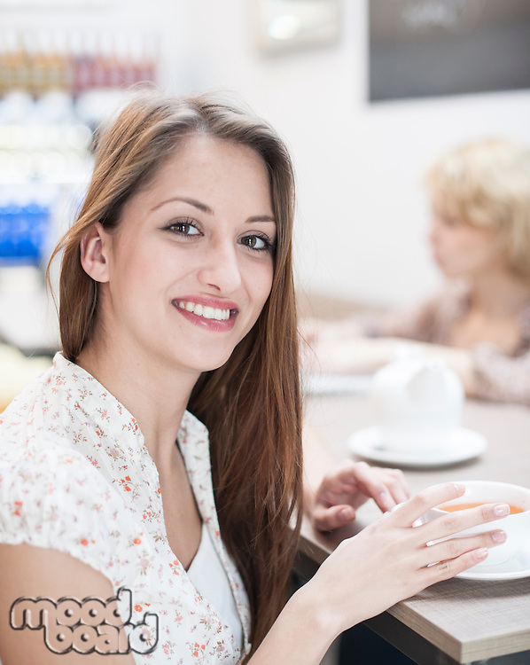 Portrait of beautiful young woman having coffee at table in cafe