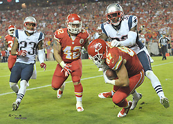 Sep 29, 2014; Kansas City, MO, USA; Kansas City Chiefs tight end Travis Kelce (87) catches a pass for a touchdown as New England Patriots free safety Devin McCourty (32) makes the tackle during the second half at Arrowhead Stadium. The Chiefs won 41-14. Mandatory Credit: Denny Medley-USA TODAY Sports