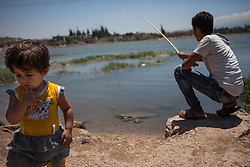 Syria.<br /> A young girl standing at a small lake looks at the photographers camera while A syrian resident of Al-Qala tries to fish with a small stick in a small lake  in the town of Al-Qala a small town with an ancient castle occupied by the Syrian regime in Hama province, Syria,<br /> 15th June 2013<br /> Picture by Daniel Leal-Olivas / i-Images