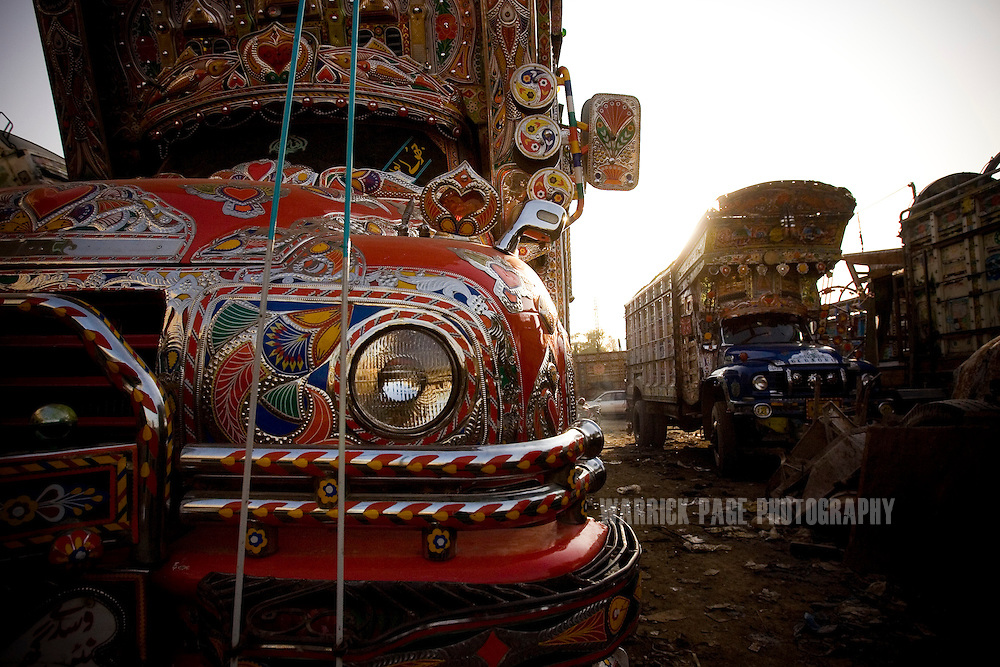RAWALPINDI, PAKISTAN - OCTOBER 9: Garishly painted Pakistani Bedford trucks await repairs and touch-up at a painting and repair yard, October 9, 2008, in Rawalpindi, Pakistan. The heavily adorned Bedford trucks have become a national icon and cost upwards of one million rupees (USD$12,500) for a full makeover. Much of the artwork consists of a cultural mix of religious and secular, Pakistani film and music stars, cricket legends, romanticized military imagery of F-16 fighter jets and Ghauri missiles, the Prophet's winged horse, Buraq, and dreamlike scenes of wooded lakes and snow-capped mountains and exotic animals. (Photo by Warrick Page)