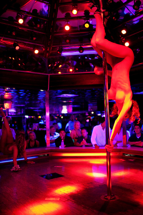 A dancer hangs upside down from the pole at the world famous Mons Venus strip club in Tampa, Florida.
