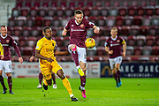 Steven MacLean (#18) of Heart of Midlothian FC gets to the ball ahead of Marvin Bartley (#6) of Livingston FC during the Ladbrokes Scottish Premiership match between Heart of Midlothian FC and Livingston FC at Tynecastle Park, Edinburgh, Scotland on 4 December 2019.