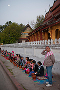 Luang Prabang, Laos. Tourists kneel, waiting to offer sticky rice to passing monks, as do villagers throughout this largely Buddhist nation. Every morning at dawn, Buddhist monks walk down the streets collecting food alms from devout, kneeling Bhddhists, and some tourists. They then return to their temples (also called wats) and eat together. This procession is called Tak Bat, or Making Merit.