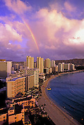 Image of Waikiki Beach and resorts along coastline with rainbow, Honolulu, Oahu, Hawaii.  For editorial captioning, please acknowledge the view from the Sheraton Waikiki Hotel