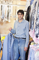 Portrait of young male sales clerk holding shirt