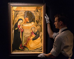 "© Licensed to London News Pictures. 02/12/2016. London, UK. A technician shows ""Nativity"" by Bicci di Lorenzo, , a 15th century, Italian gold-ground 'gabella' panel, (est. GBP 300-500k), at a preview of Sotheby's upcoming Old Masters Evening Sale in New Bond Street. Photo credit : Stephen Chung/LNP"