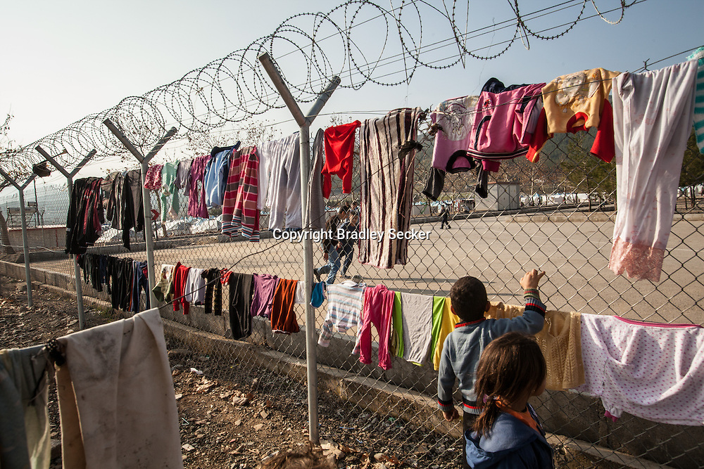 Young children watch a football game between clothes drying on a fence in Islahiye refugee camp for Syrians in southern Turkey. 02/01/2013