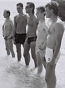 Five men lined up in the sea, Spain, 1985