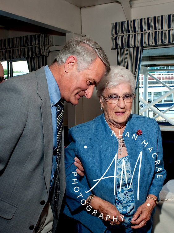 Gemma Hamel is escorted to the podium by her son, Laconia City Councilor Bob Hamel to receive the James Irwin Award at last night LRCC event aboard the MS Mount Washington.  (Alan MacRae/for the Citizen)