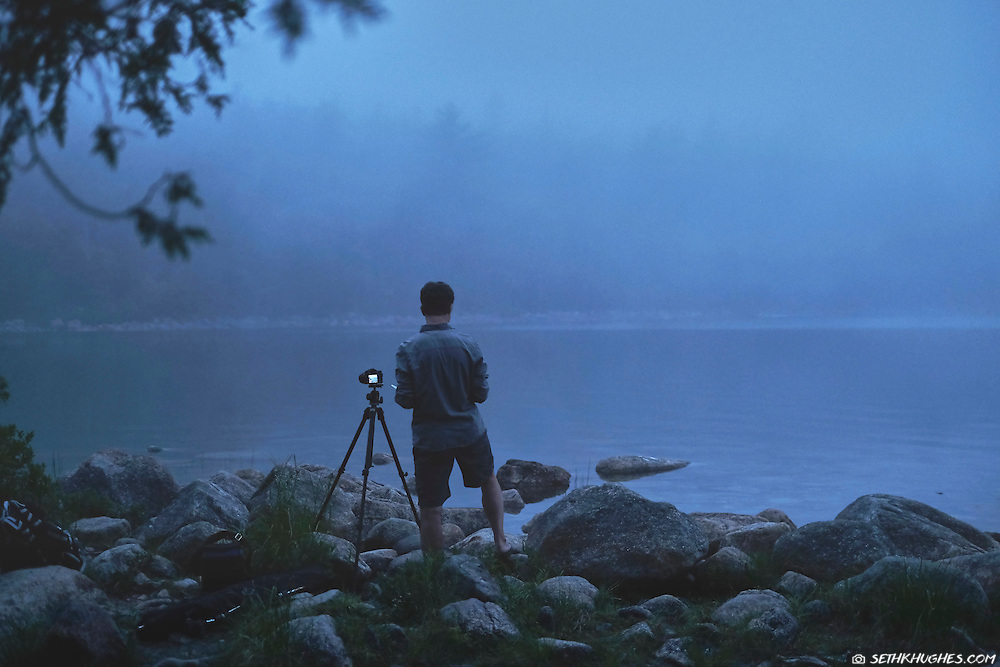 A photographer stands with a tripod and camera on the rocky beach at Jordan Pond in Acadia National Park, Maine.