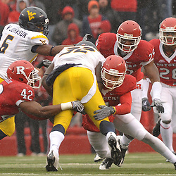Dec 5, 2009; Piscataway, NJ, USA; Rutgers cornerback David Rowe (4) and linebacker Steve Beauharnais (42) tackle West Virginia running back Ryan Clarke (32) during first half NCAA Big East college football action between Rutgers and West Virginia at Rutgers Stadium.