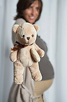 Pregnant woman holding up teddy bear indoors