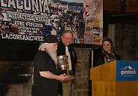 "K. Peddlar Bridges receiving a trophy for his ""historian"" work from Charlie St. Clair and Jennifer Anderson during the kickoff event at Gunstock on Thursday.  (Karen Bobotas/for the Laconia Daily Sun)"