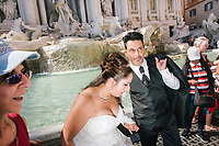 """ROME, ITALY - 20 JUNE 2017: A just married couple stops by the Trevi Fountain in Rome, Italy, on June 20th 2017.<br /> <br /> The warm weather has brought a menacing whiff of tourists behaving badly in Rome. On April 12, a man went skinny-dipping in the Trevi fountain resulting in a viral web video and a 500 euro fine.<br /> <br /> Virginia Raggi, the mayor of Rome and a national figurehead of the anti-establishment Five Star Movement,  issued an ordinance involving harsher fines for eating, drinking or sitting on the fountains, for washing animals or clothes in the fountain water or for throwing anything other than coins into the water of the Trevi Fountain, Bernini's Four Fountains and 35 other city fountains of artistic or historic significance around the city.  """"It is unacceptable that someone use them to go swimming or clean themselves, it's an historic patrimony that we must safeguard,"""" Ms. Raggi said."""