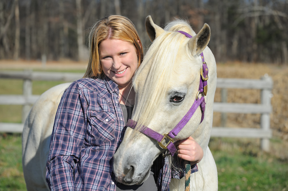 Country girl with her white Arabian horse in casual outdoor portrait in sunlight, Pennsylvania, USA.