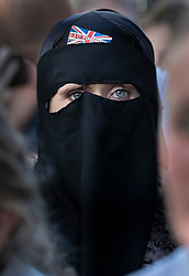 © Licensed to London News Pictures . 27/09/2018. London, UK. A woman wearing a full face veil waits to catch sight of former EDL leader Tommy Robinson after he left the Old Bailey , where his retrial for Contempt of Court was adjourned - following his actions outside Leeds Crown Court in May 2018 . Robinson was already serving a suspended sentence for the same offence when convicted in May and served time in jail as a consequence , but the newer conviction was quashed by the Court of Appeal and a retrial ordered . Photo credit: Peter Macdiarmid/LNP