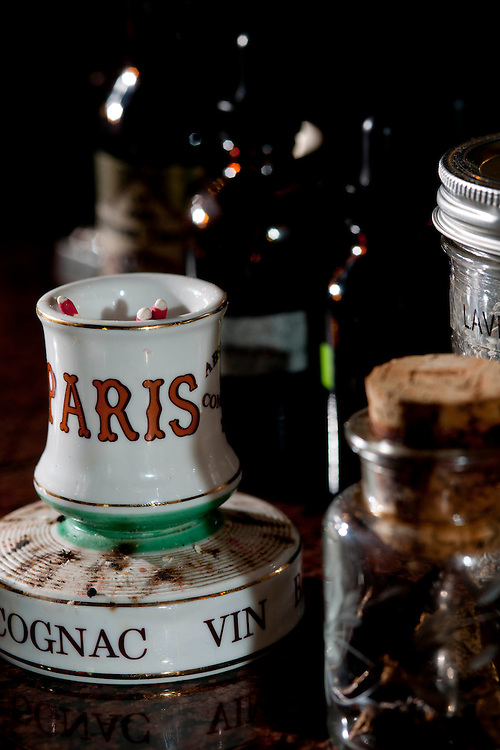 White ceramic container holding loose matches with gold trim and the words Paris, cognac, and vin sitting on the bar at Peche's Restaurant and Bar. Brown bottles with droppers in the background and jars with dried coctail enhancers in foreground.